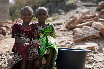 Foto auf Gartenposter Cappuccino Two Gorgeous African Black Women Sitting Outdoors with Water Bucket