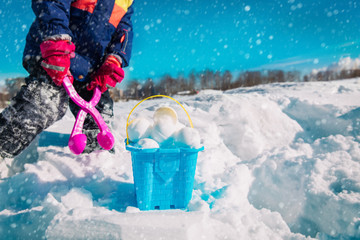 child making snowballs in winter nature, kids play outdoors