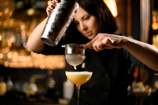 Bartender prepares cocktail drink with a sieve