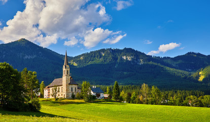 Austria mountain landscape. Traditional church chapel village. Scenic evening sunset panoramic view in austrian Alps mountains. Summer green lawns fields. Knolls covered forest trees. Blue sky clouds.