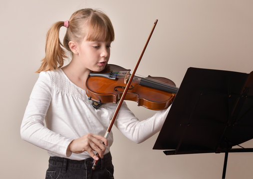 Girl playing violin looking at the score on music stand