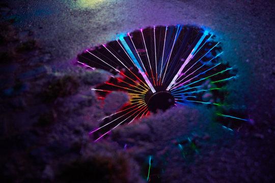 Buntes Neonlicht als Reflexion im Wasser einer Pfütze