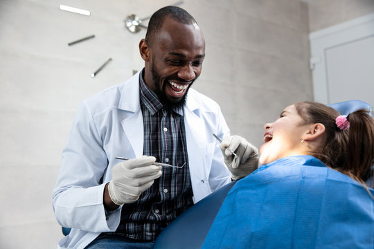 Young caucasian girl visiting dentist's office for prevention and treatment of the oral cavity. Child and african-american doctor while checkup teeth. Healthy lifestyle, healthcare and medicine