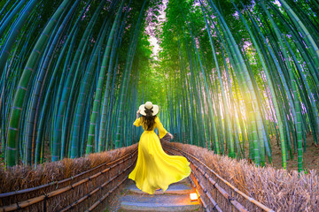 Fotorolgordijn Bamboo Asian woman wearing yellow dress to visit bamboo forest in Kyoto, Japan.