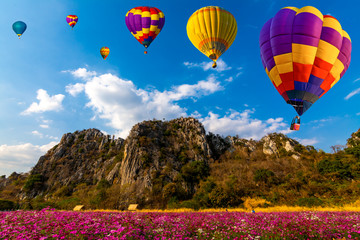 Poster Ballon Beautiful colors of the hot air balloons flying over on the hill in the cosmos flowers field background