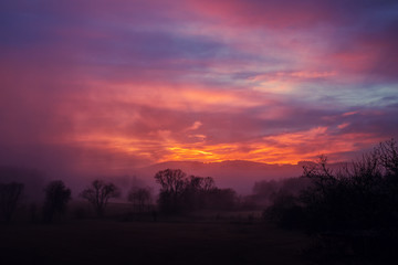 sunset in the mountains - red sky above hilly landscape