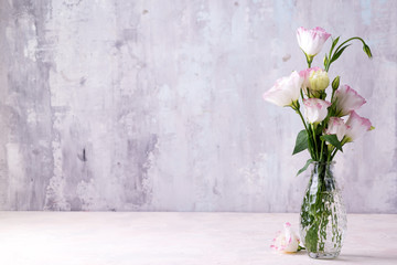 Poster Floral Eustoma flowers in vase on table near stone wall, space for text. Blank for postcards