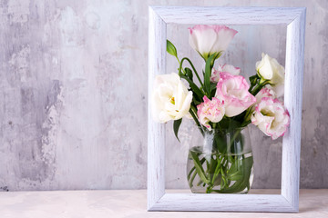 Foto op Canvas Bloemen Eustoma flowers in vase in photo frame on table near stone wall, space for text. Blank for postcards