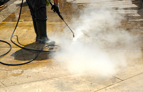 Worker cleaning with pressurized water the pavement of city streets. Covid-19 disinfection