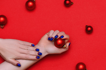 Wall Mural - Woman hands with trendy manicure holding Christmas toy on red background.
