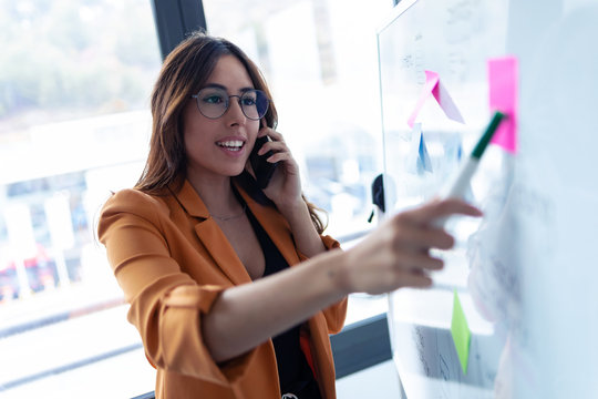 Business young woman talking on mobile phone while working on white board with post it stickers in the office.