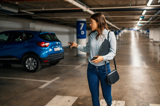Woman in a parking garage, unlocking in her car. Woman activating her car alarm in an underground garage as she walks away. Young business woman walking with car keys in the underground parking.