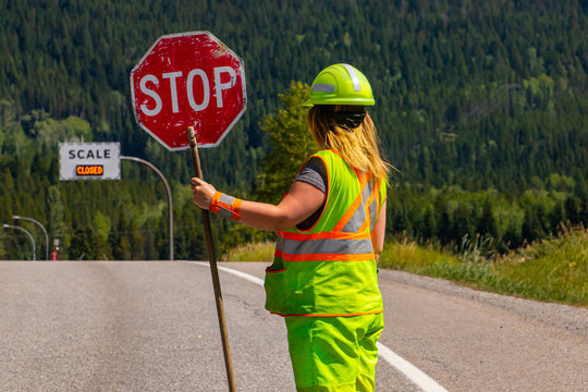 A close up and rear view of a female road construction worker holding a stop stick wearing high visibility safety clothes, roadworks traffic control