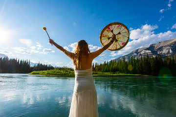 Traditional native culture meets mother nature as a mindful woman wearing a white summer dress holds sacred drum and beater by a river