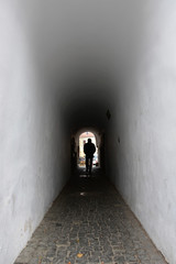 Foto auf Acrylglas Schmale Gasse Silhouette of a man passing through a narrow alley / archway in the old town of Sibiu, Romania
