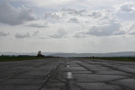 Wet abandoned runway near Sapareva Banya, Bulgaria, nowadays used as rally racetrack. Dark cloudy day.