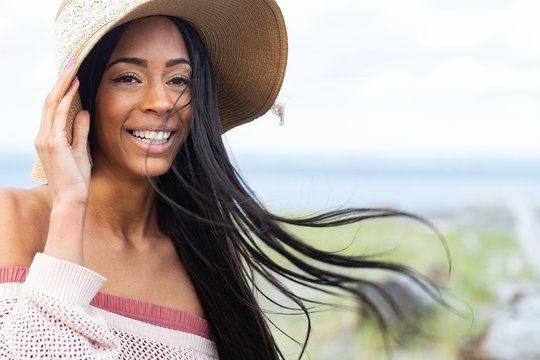 Pretty African American woman with long black hair at the beach