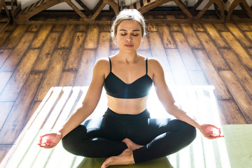 Young woman meditating sitting in lotus position