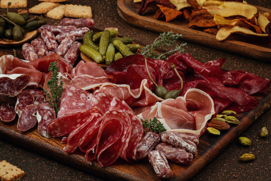 Appetizers table with differents antipasti, cheese, charcuterie, snacks and wine. Sausage, ham, tapas, olives, cheese and crackers for buffet party.
