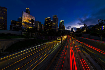 Wall Mural - JANUARY 20, 2019, LOS ANGELES, CA, USA - California 110 South leads to downtown Los Angeles with streaked car lights at sunset