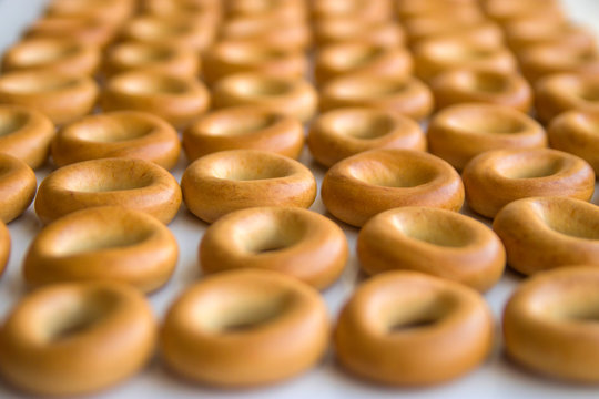 Many bagels stacked on a white kitchen table close-up