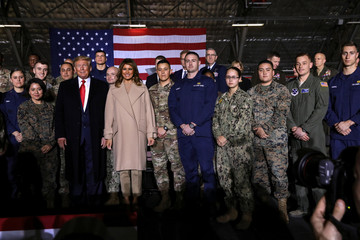 """U.S. President Donald Trump and first lady Melania Trump pose for a group photo at a signing ceremony of the """"National Defense Authorization Act for Fiscal Year 2020"""" at Joint Base Andrews"""