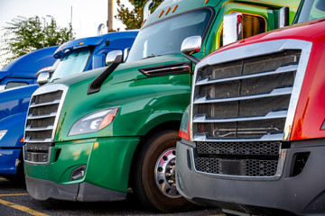 Front part of big rig semi trucks with chrome grilles and plastic bumpers standing in row on truck stop parking lot Wall mural