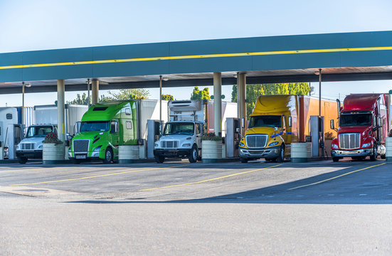 Different big rigs semi trucks standing on fuel station for truck refueling and continuation of the route