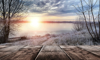 Winter background. Winter snow landscape with wooden table in front. Winter sun, ray, glare. Empty natural scene with a wooden table.