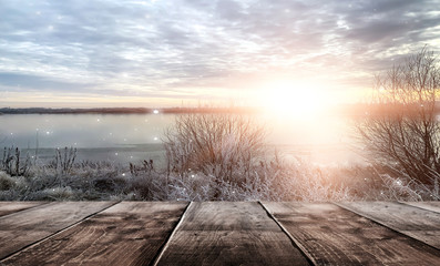Poster Wit Winter background. Winter snow landscape with wooden table in front. Winter sun, ray, glare. Empty natural scene with a wooden table.