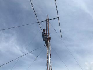 Munandar, radio communication technician, climbs as he checks tower in Banda Aceh