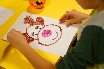 Handmade Christmas toys. Step-by-step. Making Christmas deer. Children holiday crafts. Top view. The child paints the deer