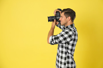 Professional photographer working on yellow background in studio. Space for text Fotobehang