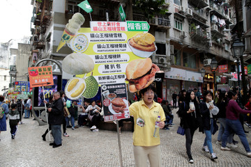 Restaurant sales assistants holding signs wait for customers at a street in Macau