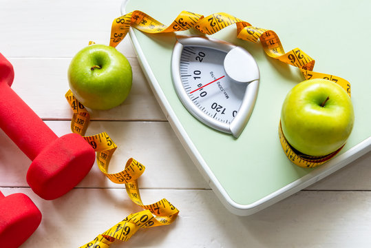 Diet and Healthy life loss weight Concept. Green apple and Weight scale measure tap with fresh vegetable and sport equipment for women diet slimming.