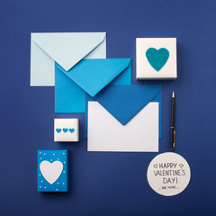 Blue envelopes, gifts and white hearts on classic blue