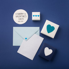 Blue envelope, gifts and white hearts on classic blue