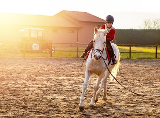 8 year boy riding white horse during sunset at ranch