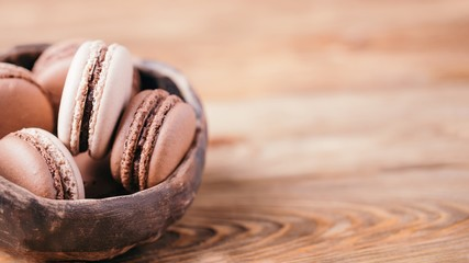 Poster Macarons Homemade chocolate and vanilla macaroons in a ceramic bowl on a wooden background. Copy space, 16:9