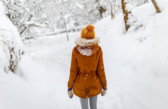 girl or woman walk in winter outdoor, snowy cold weather, countryside blizzard snowfall, yellow hat