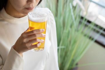 In de dag Alcohol グラスに注がれたビールを持つ若い女性の手元