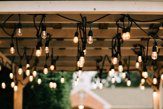 Hanging vintage string lights w on a wooden pergola beams patio in a backyardith edison bulbs