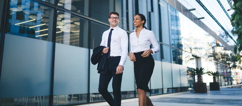 Relaxed young coworkers walking on street Low angle of happy young diverse woman and man in elegant outfits walking and chatting cheerfully on background of city building