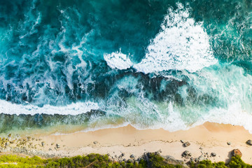 Wall Murals Bali View from above, stunning aerial view of a rocky shore with a beautiful beach bathed by a rough sea during sunset, Nyang Nyang Beach (Pantai Nyang Nyang), South Bali, Indonesia.