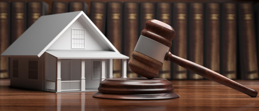 House model and auction judge gavel on a wood desk, law books background. 3d illustration