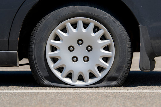 Flat tire on an unidentifiable black car. Low angle closeup view. No markings or identification on the car or tire.