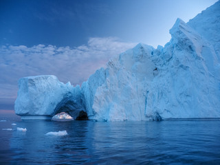 Iceberg at sunset. Nature and landscapes of Greenland. Disko bay. West Greenland. Summer Midnight Sun and icebergs. Big blue ice in icefjord. Affected by climate change and global warming. Fotoväggar