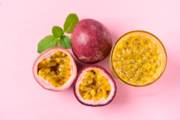Fresh passion fruit and juice on pink background, top view