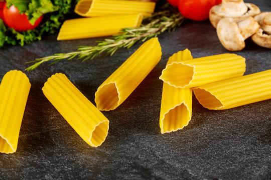 Dry manicotti pasta with mushrooms and tomato.