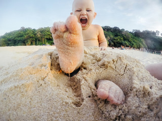 Emotional portrait of a one-year-old child playing in the sand on the beach in summer. Screams and emotions.